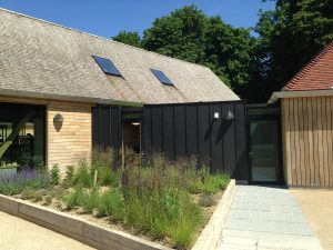 Black Zinc cladding, pitched, tiled roofs and sweet chestnut shake roof at the open air museum in Chichester.