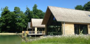 View of visitors centre next to a picturesque lake with roofs covered in handmade cedar shakes installed by Kingsley Roofing